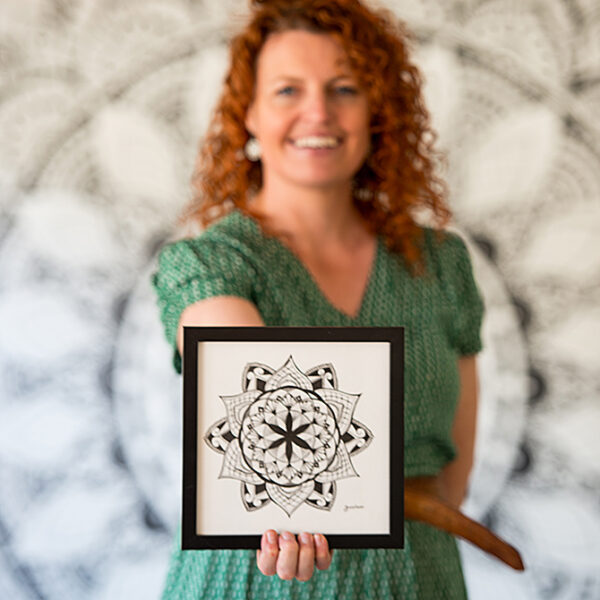 kylie holding her artwork infront of the wall mandala