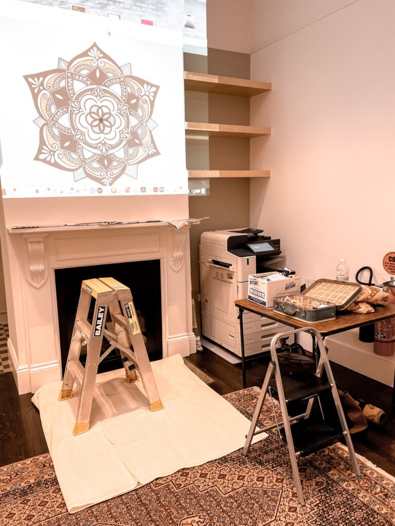 image of the wall above the fire place with a projection of the design on the wall there is a ladder infront of the fireplace and a table beside with all the tools on it ready for painting